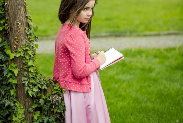 Pretty little girl poetess in dress and jacket with long brunette hair holding notebook and pen standing near tree with green creeper vine on grass